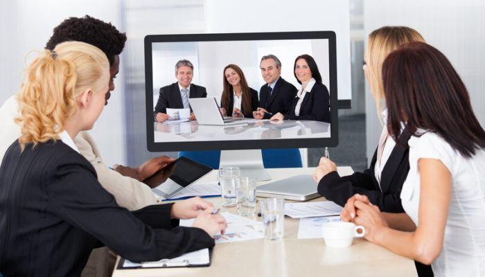 This photo shows a group of four people in business clothing gathered around a beige worktable, looking up at a screen showing four more business people in a different room, representing the best video conferencing affiliate programs.