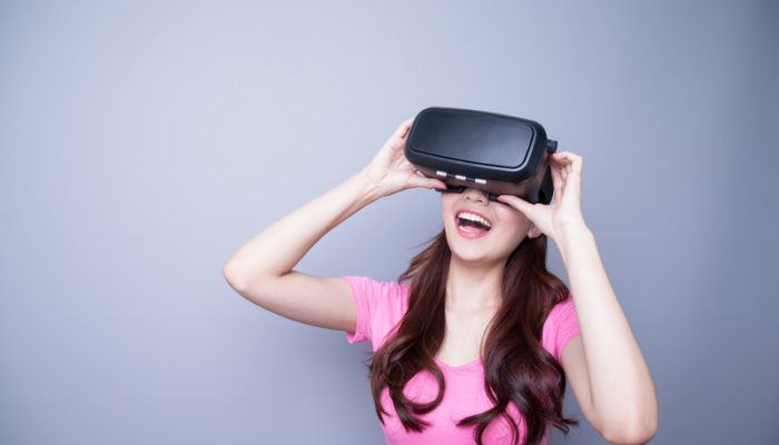 This photo shows a smiling woman with long brown hair and a pink shirt holding a set of virtual reality glasses up to her eyes in front of a gray background, representing the best virtual reality affiliate programs.