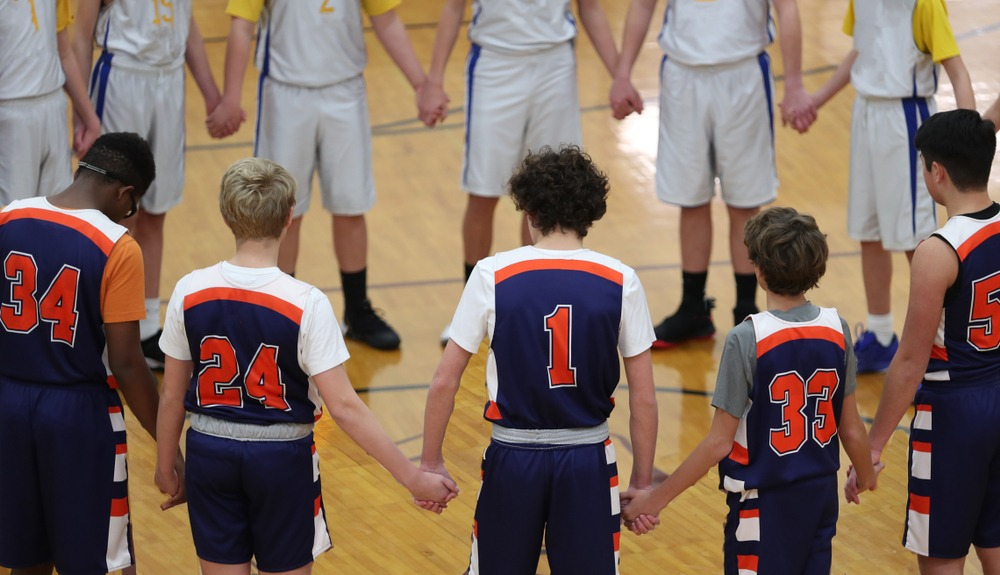 Christian Youth basketball team holding hands before game