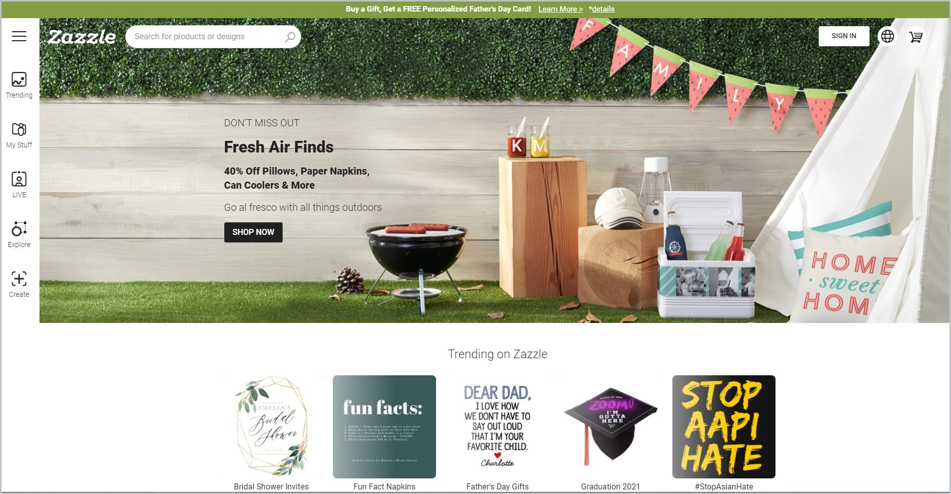 screenshot of Zazzle homepage with lime green announcement bar, and an image of a backyard picnic setup