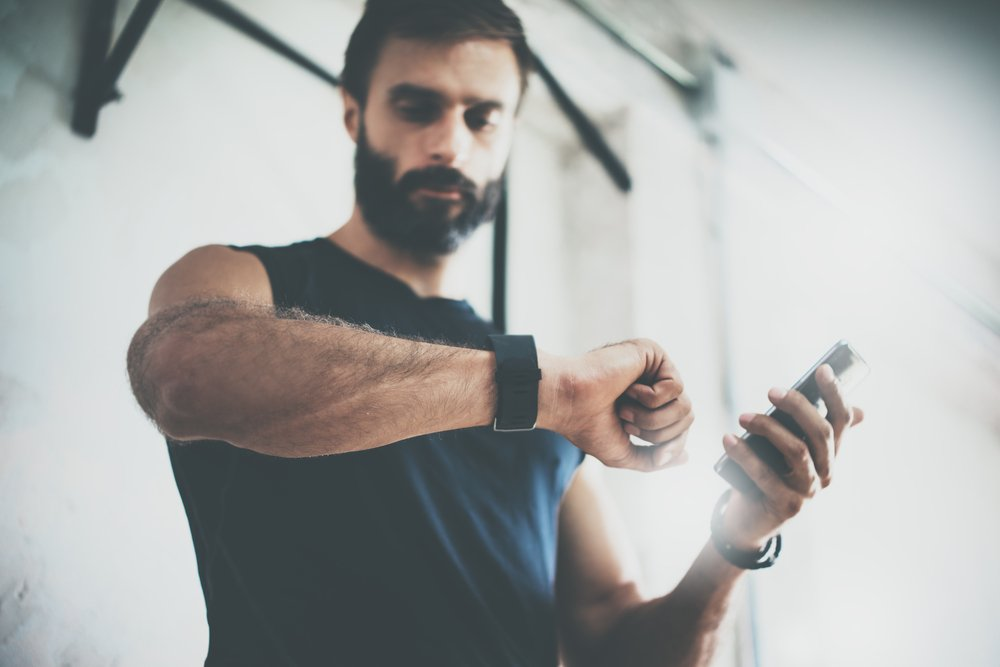 bearded man looking at fitness watch and smartphone