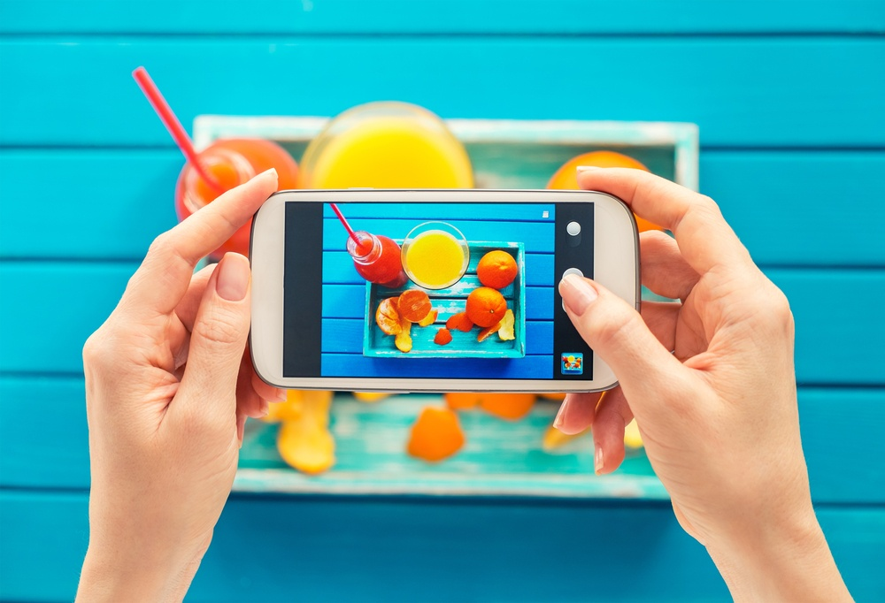 blogger taking colorful photograph for instagram using a smarthpone