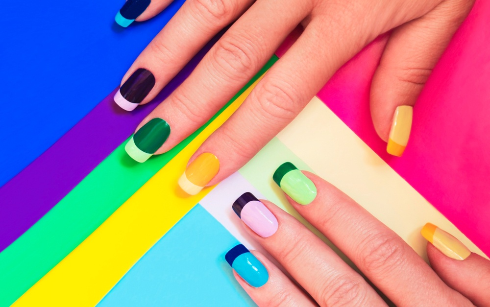 brightly colored fingernails on neon color variated background