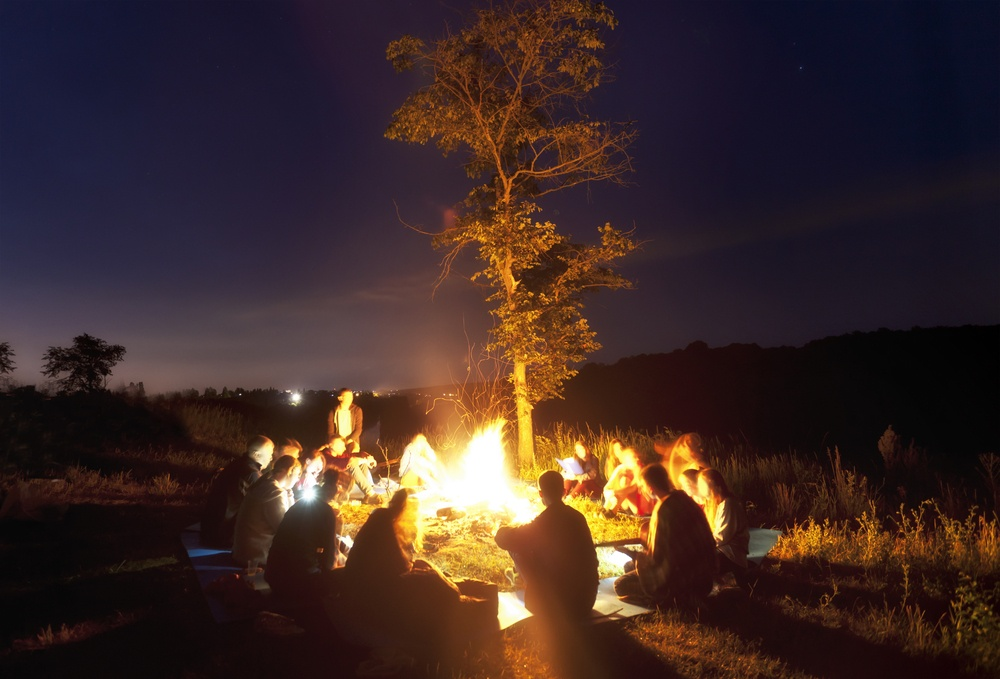 christian youth sitting around a camp fire