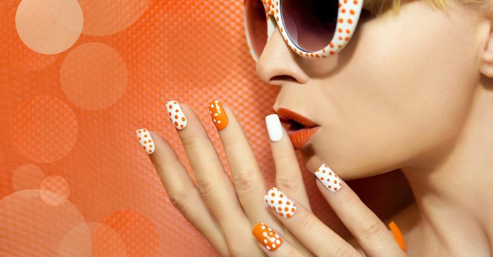 fashionable woman with orange polka dot nail art and sunglasses