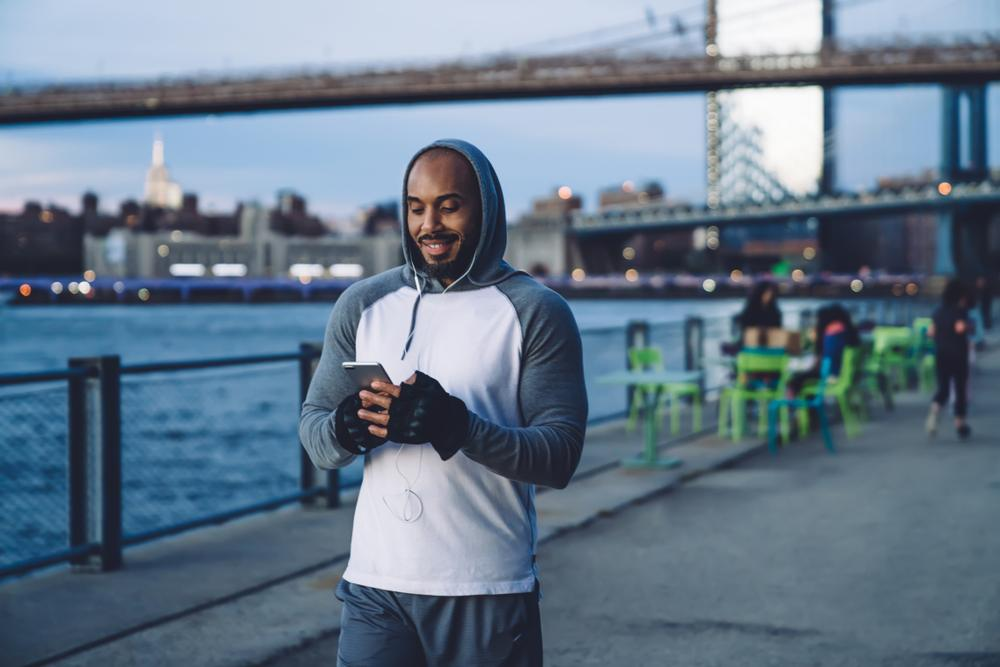 fitness blogger engaging with fans on his smartphone with social media