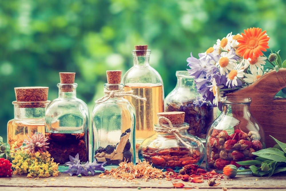 hazy filter image of antique essential oil bottles with flowers