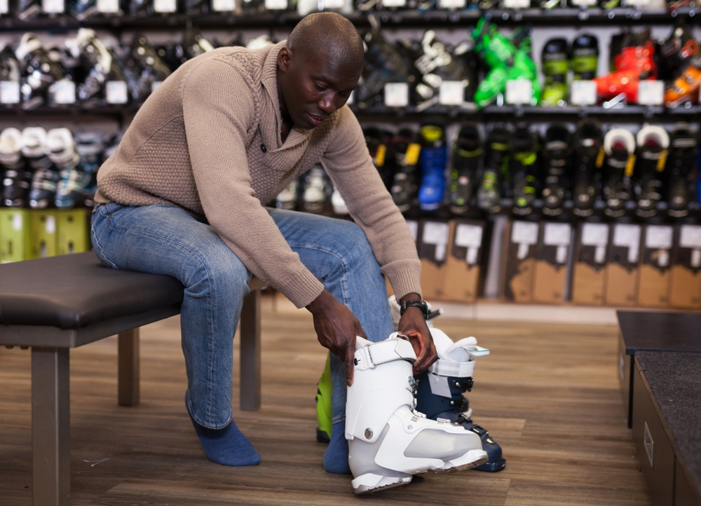 man buying ski boots in store