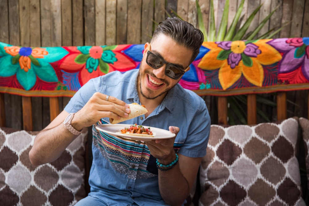 man with modern sunglasses and dark hair eating a taco with brightly colored material in background
