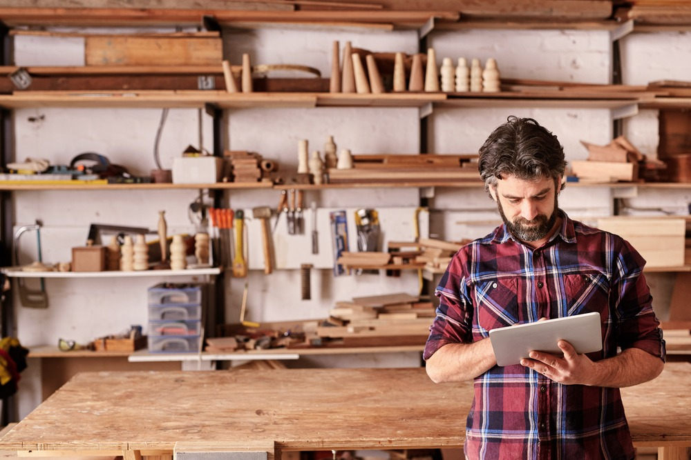 middle aged man with woodworking business and tablet for orders