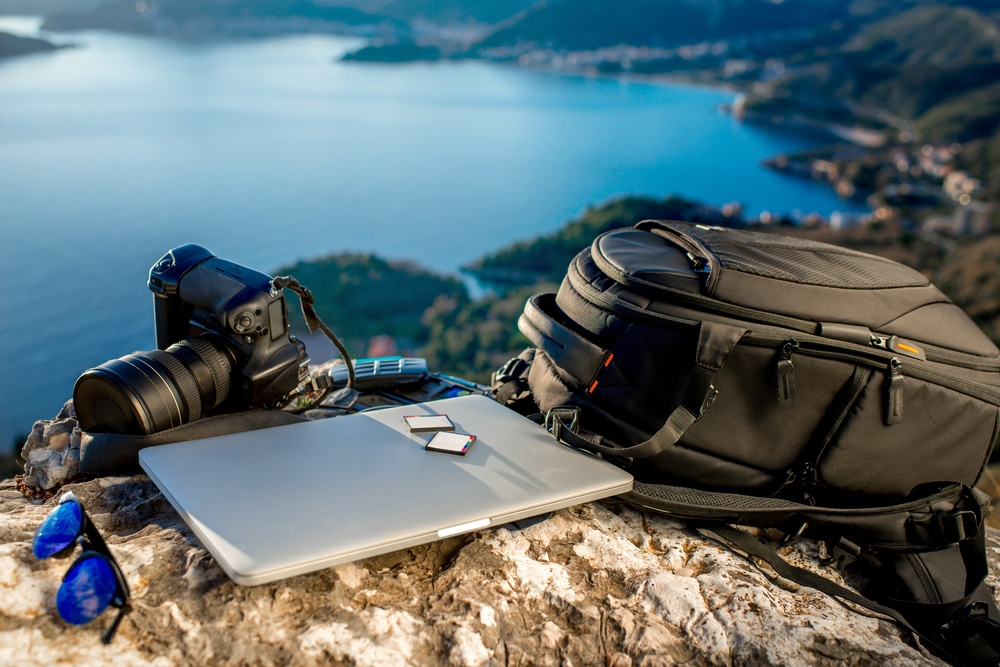 photography blogger traveling with laptop and dslr camera with zoom lens
