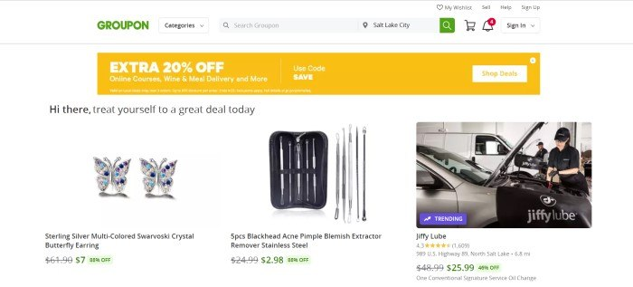 This screenshot of the home page for Groupon has a white header and background, a yellow sales bar, and a row of products for sale, including butterfly earrings, hygiene products, and an oil change.