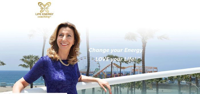 This screenshot of the home page for Life Energy Coaching has a gold logo above a photo of a smiling brunette woman in a blue shirt leaning against a balcony that overlooks a beachfront amusement park, along with white text inviting customers to change their energy and love their lives.