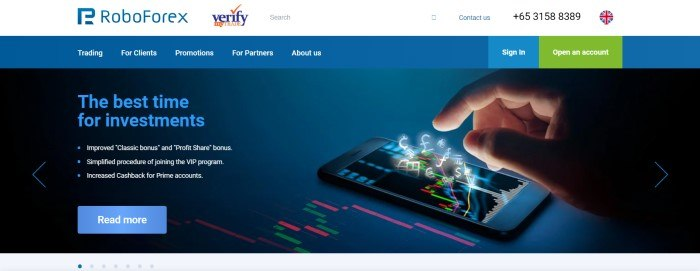 This screenshot of the home page for RoboForex has a white header, a blue navigation bar, and a photo of a man's hand about to tap a mobile device that has electronic currency symbols floating out of the screen, along with blue and white text announcing the best time for investments and a blue call to action button.