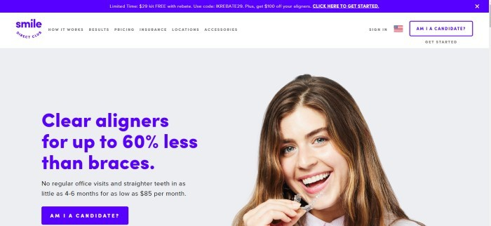 This screenshot of the home page for Smile Direct has a blue header, a white navigation bar, and a photo of a smiling brunette woman holding a clear aligner in her hand, along with blue and black text announcing clear aligners and a blue call-to-action button.