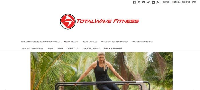 This screenshot of the home page for Total Wave Fitness has a white background with a red logo and black text in the navigation bar, as well as a photo of a blonde woman with a focused look on her face using a the Total Wave machine in front of a backdrop of tropical plants.