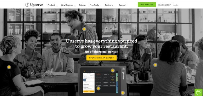 This screenshot of the home page for Upserve has a white header and navigation bar with a green call to action button above a black and white photo of the inside of a restaurant, with a table of three people talking to a smiling waiter with pen and pad in hand, as well as several other tables of happy people, along with white text and a yellow call to action button.