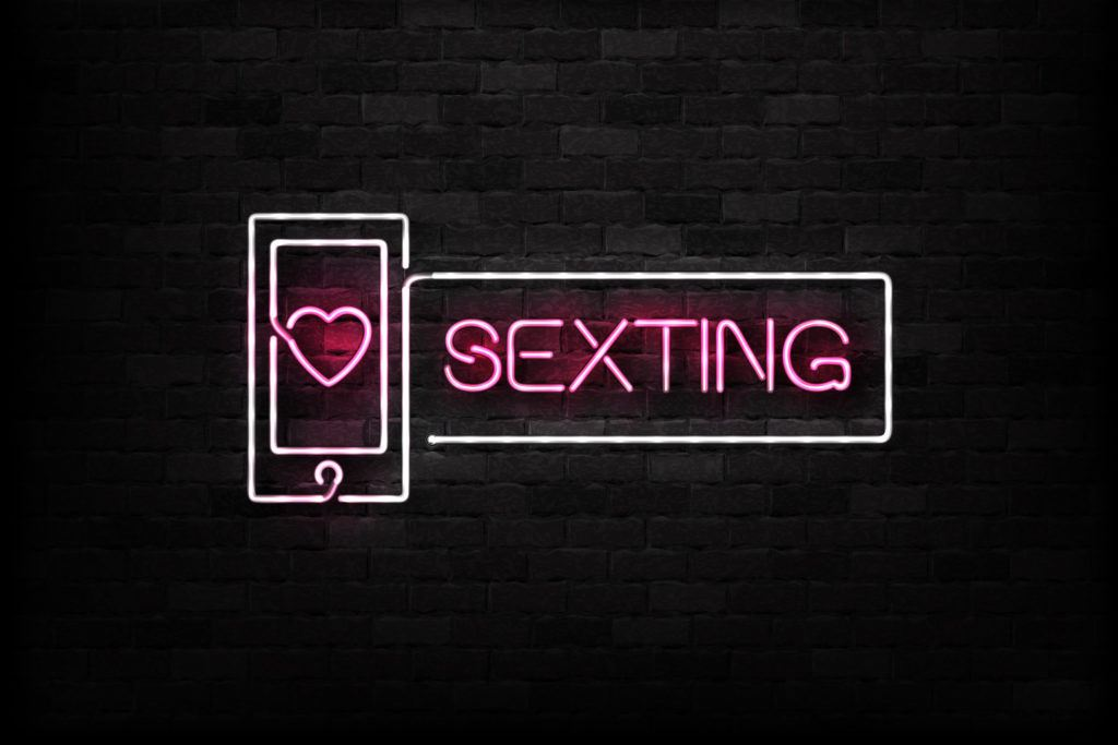 sexting sign in neon with pink text and white outline