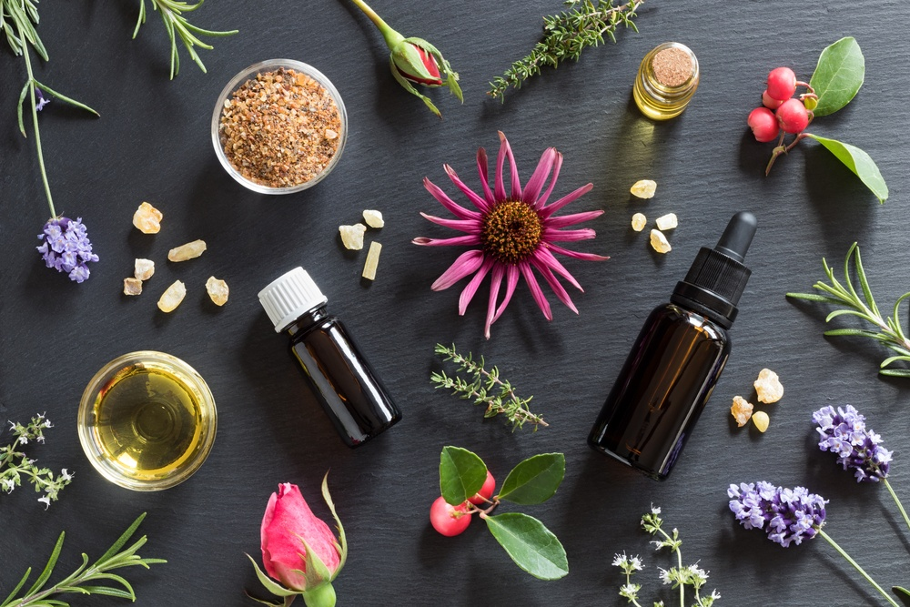 visually stunning mix of herbs, flowers, berries, and oils on black background