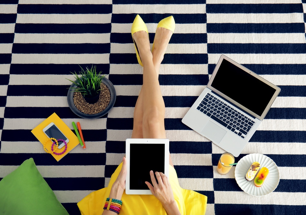woman searching on fashion blog with yellow dress and multiple internet connected devices