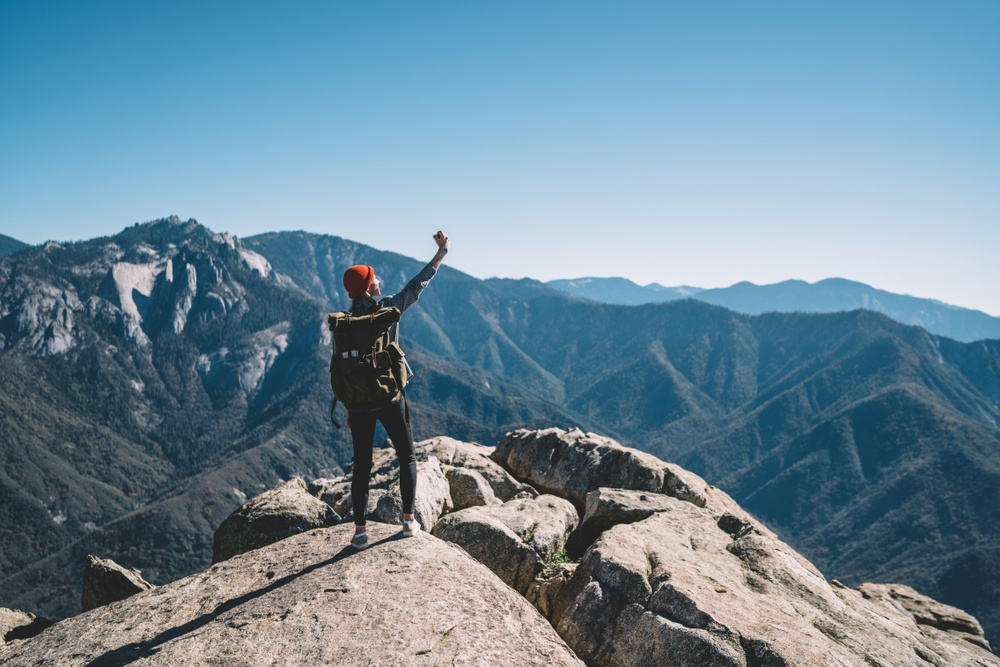 woman with backpack standing on top fo a rock with huge mountains in the background