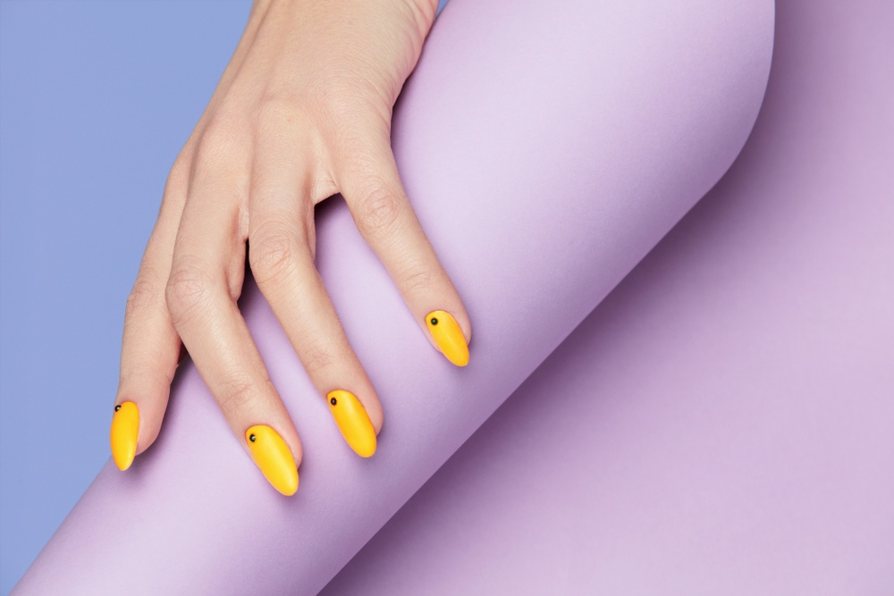 yellow designer nails with pastel purple background