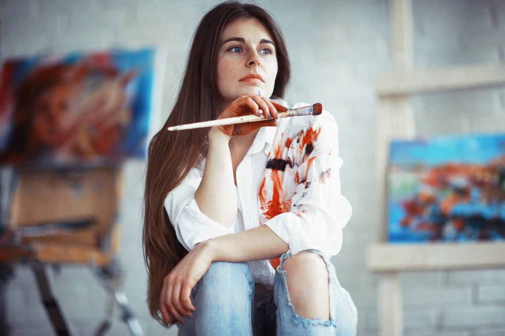 young artist with paint on white shirt with canvases in the background