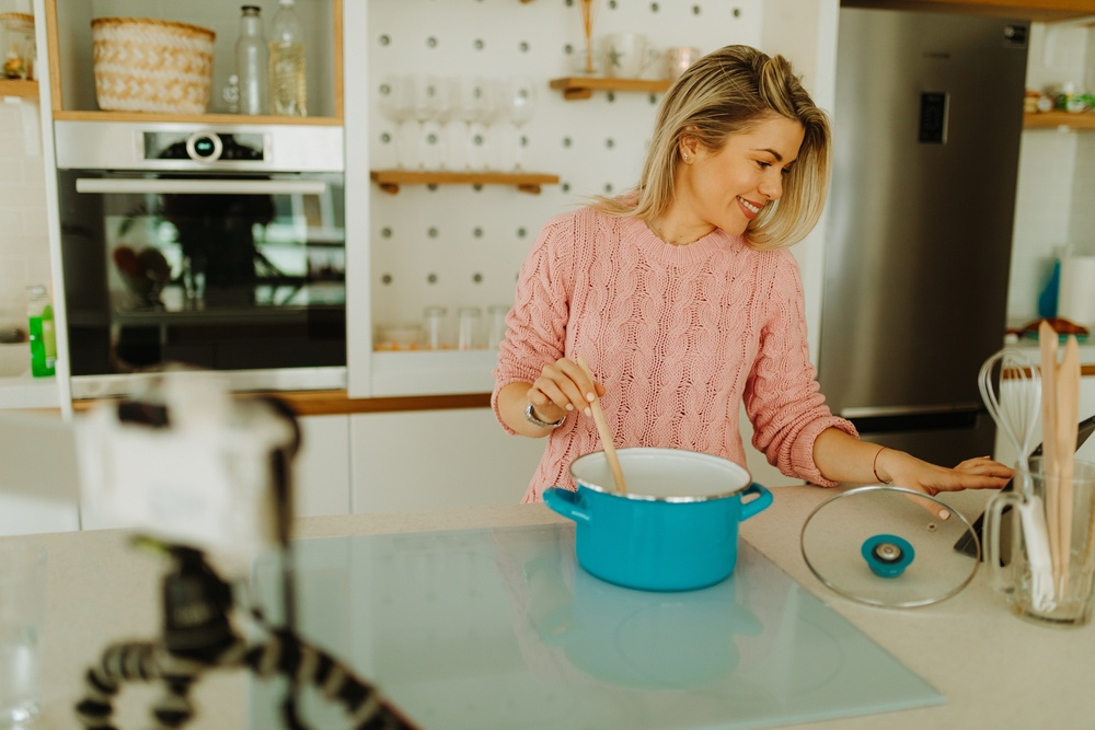 young blond woman using teal cookware and searching for online recipe on iPad