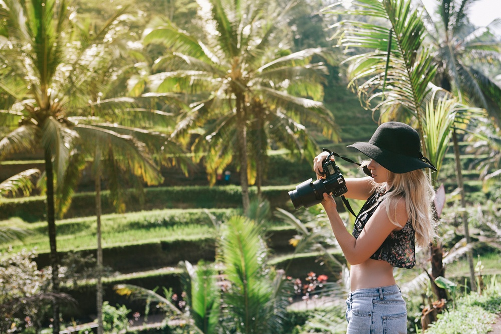 young blonde with short shirt looking at dslr camera in jungle garden setting