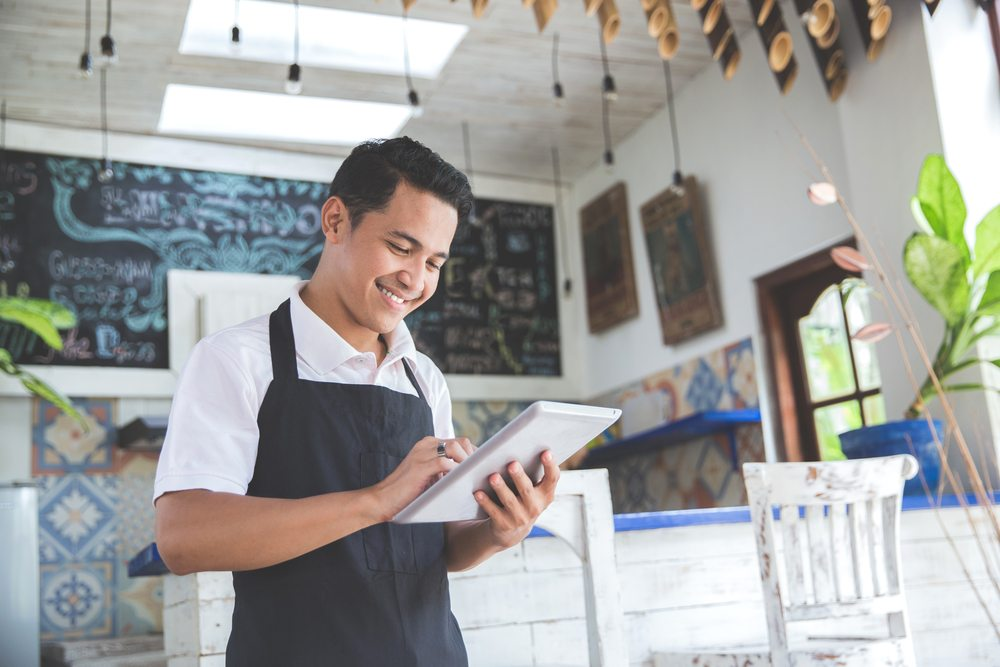 young latino man in cafe managing his business on a tablet