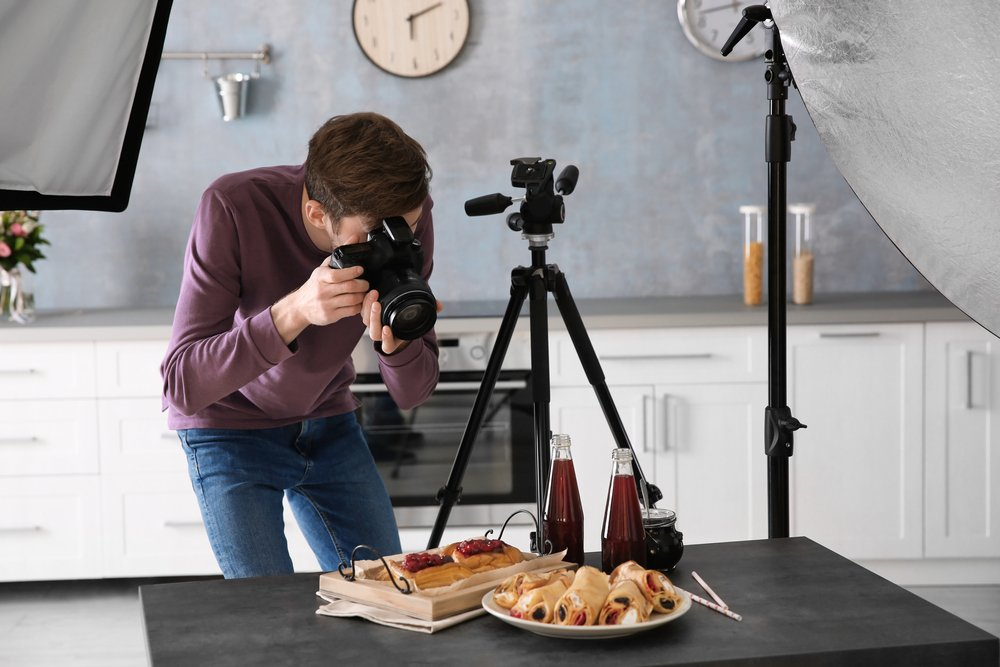 young man taking photos of dessert pastries and drinks with dslr camera