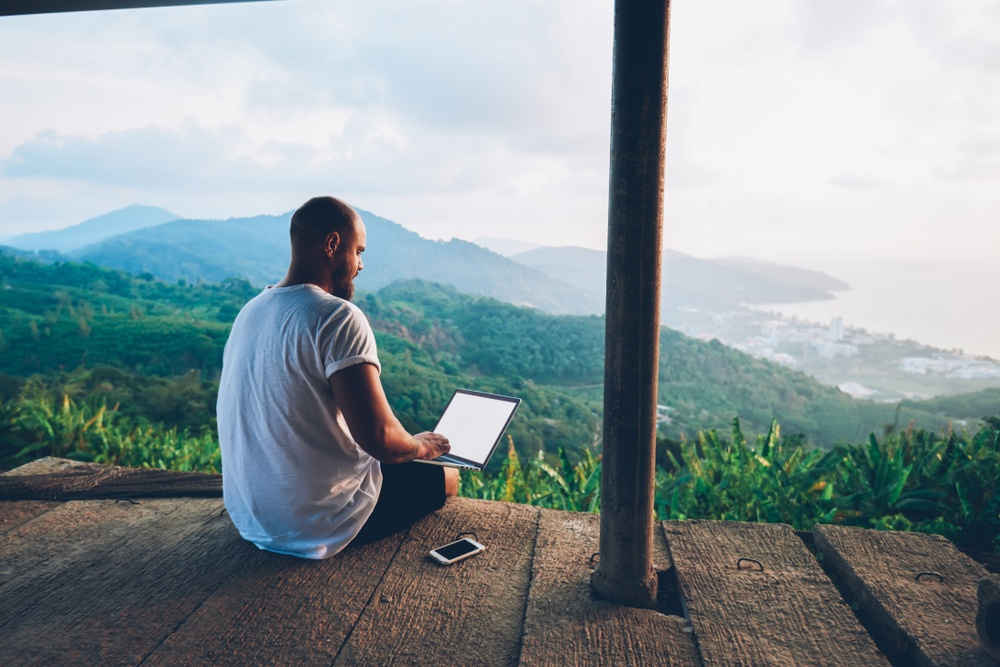 young man wish shaved head and beart sitting on deck above mountains