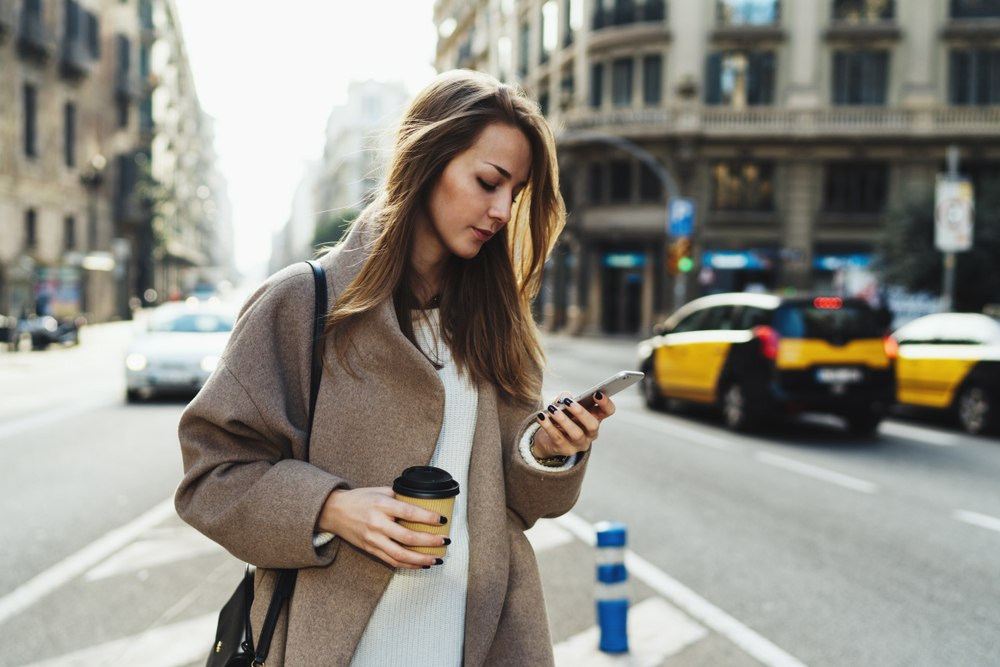 young woman looking seriously at phone in the middle of traffic in the city