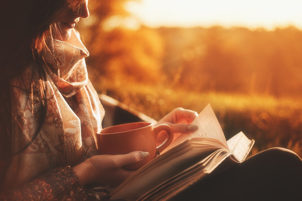 young woman reading a book at sunrise with cup of coffee