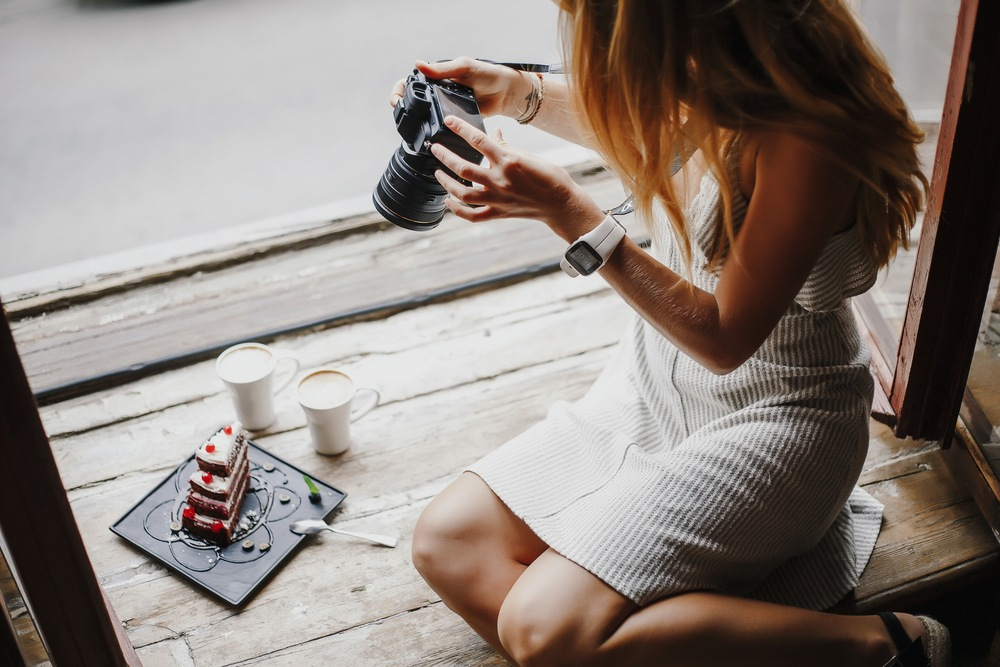 young woman taking professional photos of layered cake with coffee sitting on wooden window sill