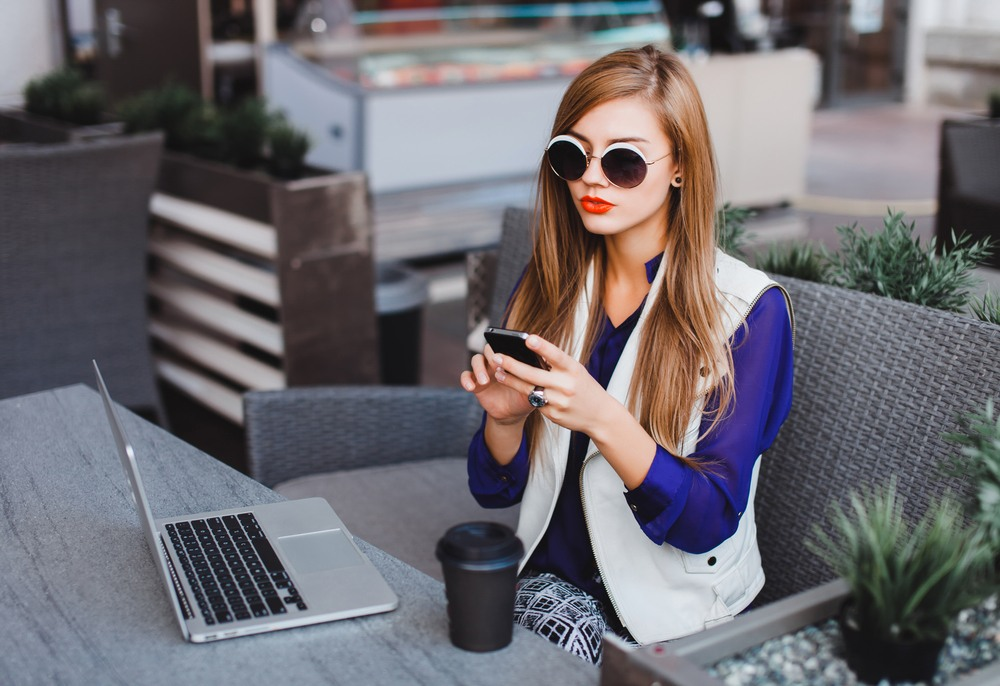 young woman with fashionable sunglasses reading online blog about fashion
