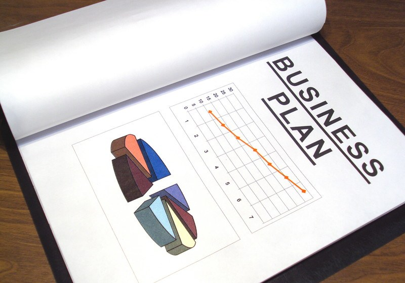 This photo shows an open business plan with a line chart and a pie chart lying on a wooden table, representing the best business plan affiliate programs.