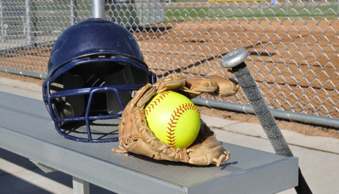 This photo shows a dark blue helmet, a brown mitt, a black bat, and a yellow softball on or near an aluminum bench in front of a chain-link fence near a softball field, representing the best softball affiliate programs.