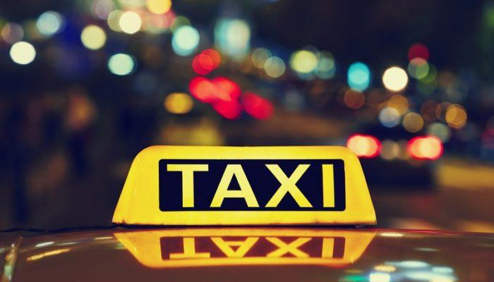 This photo shows the a yellow and black light bar reading 'Taxi' on the top of a car in front of blurry city lights in red, blue, green, orange, and white against a dark sky, representing the best taxi affiliate programs.