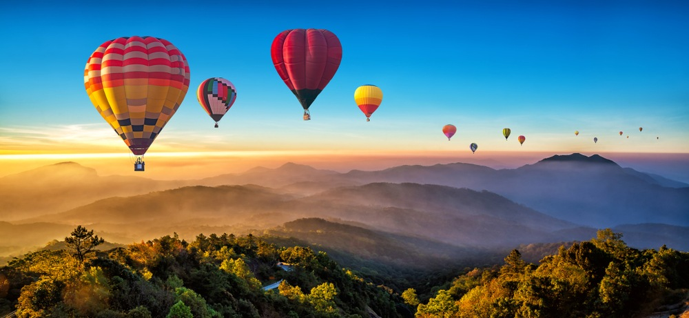 colorful hot air balloons floating over sunset mountains