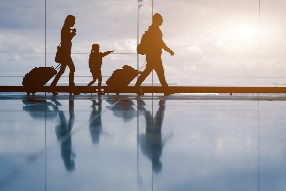 family silhouette in airport with child pointing at sky