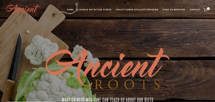 This screenshot of the home page for Ancient Roots has a dark filtered photo of a cutting board, knife, and head of cauliflower on a dark wooden table, along with a transparent navigation bar and text in orange and white.