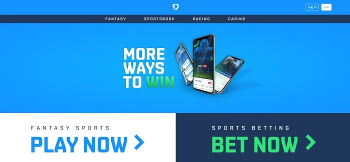 This screenshot of the home page with a blue background, a dark blue navigation bar with white text, a photo of three mobile devices with the app on the screens, with white and green text announcing more ways to win, above a white section with black and blue text on the left announcing fantasy sports and a black section announcing sports betting on the right side of the page with white and green text.