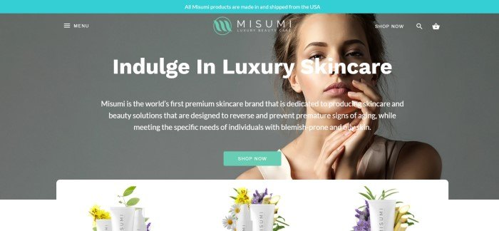 This screenshot of the home page for Misumi has an aqua header above a gray-background photo of a woman with flawless skin and white text inviting customers to indulge in luxury skincare, along with an aqua call to action button, above a row of pictures with bottles of skincare products and flowers in yellow and purple.
