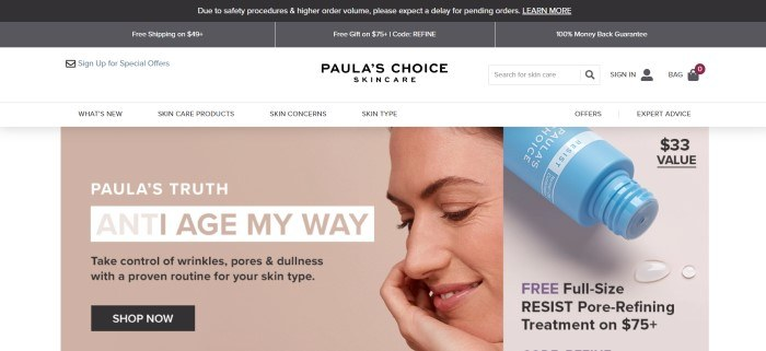 This screenshot of the home page for Paula's Choice has a black and gray header, a white navigation bar and search bar, a beige-background photo with a profile shot of a smiling woman with beautiful skin next to an advertisement in black text for anti-aging treatments, and a photo on the right side of the page for a blue bottle of a skincare product.