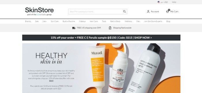 This screenshot of the home page for SkinStore has a gray and white header and navigation bar above a black discount bar and a gray-background photo containing black text describing healthy skincare products, as well as a row of three bottles of skincare products in white bottles, one with an orange label.