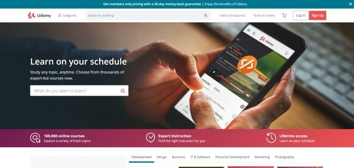 This screenshot of the home page for Udemy shows a photograph of a man's hands accessing Udemy classes on a mobile phone, behind white text inviting potential students to learn on their own schedule.