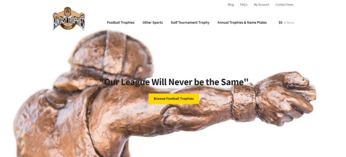 This screenshot of the home page for Fantasy Trophies has a white background and header with a brown and red logo, above a closeup photo of a bronze trophy, along with black text and a yellow call to action button.