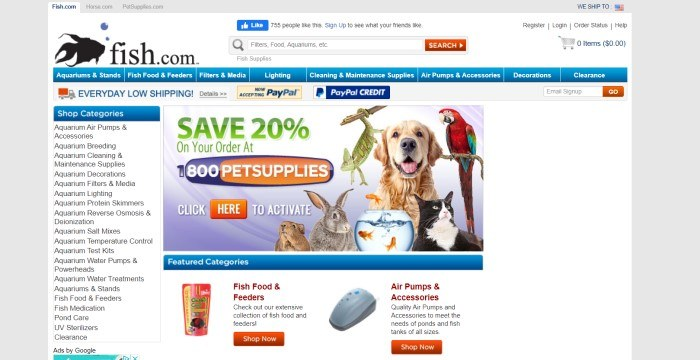 This screenshot of the home page for Fish.com has a white background and header, a blue navigation bar, a white category side menu, a photo of several pets in the center of the page behind green, orange, and white text announcing petsupplies.com, and a row of product descriptions with small photos at the bottom of the page.