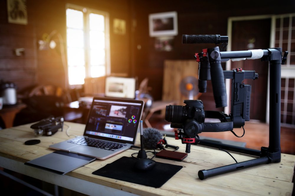 youtube vlogger equipment and hardware including laptop, mic stand, camera stand, and video editing software